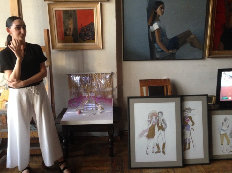 Armine in front of her own artwork and that of her grandfather Khachatur Azizyan