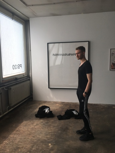 Aleksandr Blanar at A Strong Desire in front of work by Monica Bonvicini and Elmgreen and Dragset